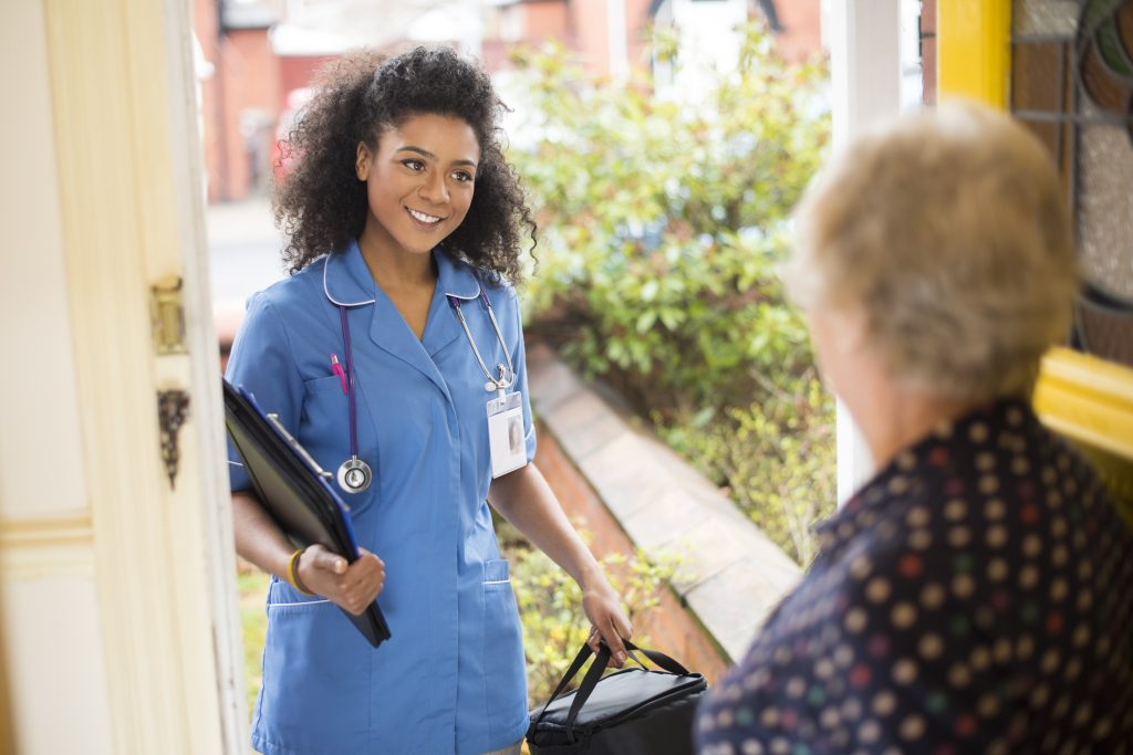 A female nurse or community care worker is leaving the front door of her senior female patient and saying goodbye. She is wearing a blue nurses tunic , and holding a medicines bag . She is wearing an ID badge with her profile photo already on it . The senior patient has her back to us at the front door . In the background a residential street can be seen defocussed .